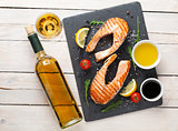 Grilled salmon and white wine on wooden table