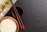 Japanese sushi chopsticks over soy sauce bowl, rice and sakura b