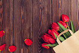 Red tulips bouquet in paper bag