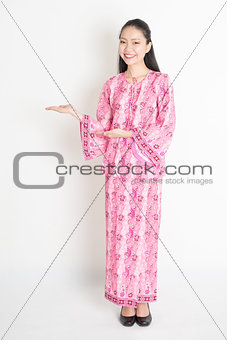 Asian girl in pink batik dress showing somethings