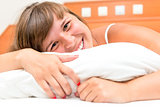 laughing beautiful girl resting in bed
