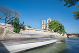Notre dame and Seine river with tourist boat, long exposure
