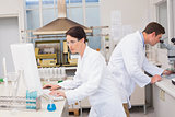 Scientists working with microscope and computer