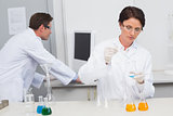 Scientist pouring chemical fluid in funnel and her colleague working with computer