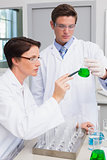 Scientists examining attentively beaker with green fluid