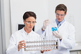 Scientists looking attentively at test tubes