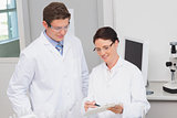 Smiling scientists looking at clipboard