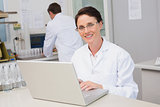 Smiling scientist using laptop