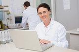 Smiling scientist using laptop