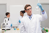 Scientist looking at white precipitate while colleagues talking together