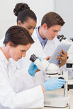 Scientists using microscope and tablet pc
