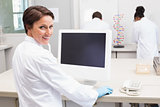 Smiling scientist using computer while colleagues working