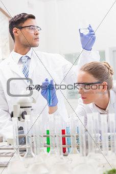 Focused scientists examining test tube and beaker