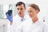 Concentrated scientists holding beaker with fluid