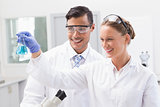 Smiling scientists looking at beaker