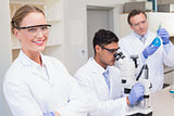Smiling scientist looking at camera while colleagues working with microscope