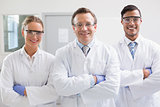 Smiling scientists looking at camera arms crossed