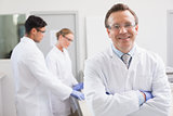 Smiling scientist looking at camera while colleagues working behind
