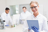 Smiling scientist using tablet while colleagues working behind