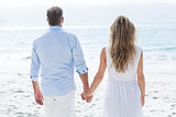 Happy couple standing by the sea and holding hands