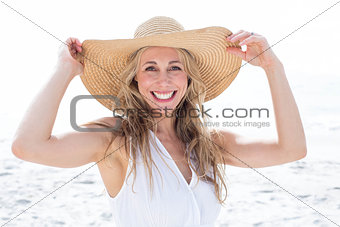 Smiling blonde in white dress looking at camera and wearing straw hat