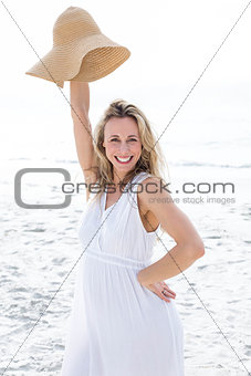 Smiling blonde in white dress looking at camera and holding straw hat