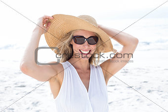 Smiling blonde in white dress wearing sun glasses and straw hat