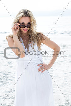 Smiling blonde in white dress wearing sun glasses