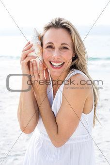 Smiling blonde in white dress listening the seashell