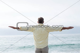 Thoughtful man standing by the sea arms outstretched