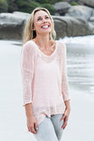 Smiling blonde standing by the sea