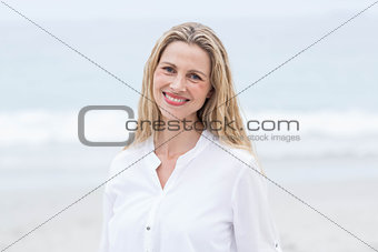 Smiling blonde standing by the sea and looking at camera
