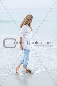 Smiling blonde walking by the sea