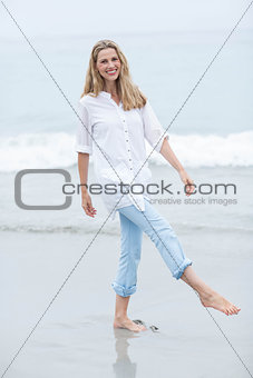 Smiling blonde walking by the sea and looking at camera