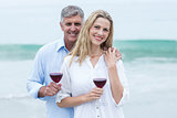 Happy couple smiling at camera and holding a glass of red wine