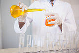 Concentrated scientist pouring orange fluid