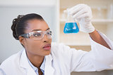 Scientist examining petri dish with blue fluid inside
