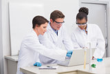 Concentrated scientists working together with laptop