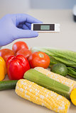 Scientist using device on vegetables