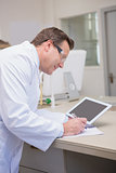 Smiling scientist holding tablet writing on notebook