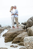 Happy couple standing on the rock and looking at each other