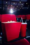 Empty rows of red seats with pop corn and drink