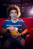 Young man watching a film and eating pop corn