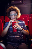 Young man watching a 3d film and drinking soda