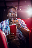Young man watching a film and drinking soda