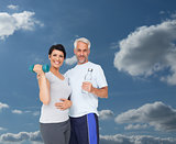 Composite image of happy fit couple with dumbbell and water bottle