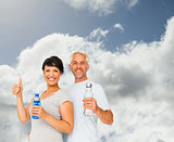 Composite image of fit couple with water bottles gesturing thumbs up