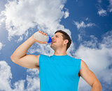 Composite image of smiling young man drinking water