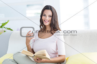 Smiling beautiful brunette holding mug and reading a book while relaxing on the couch