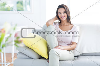 Smiling beautiful brunette relaxing on the couch and looking at camera